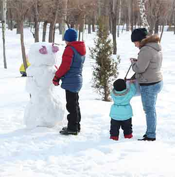 Family building a snowman in the park