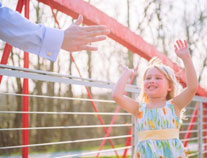 Child giving parent a high-five at the park
